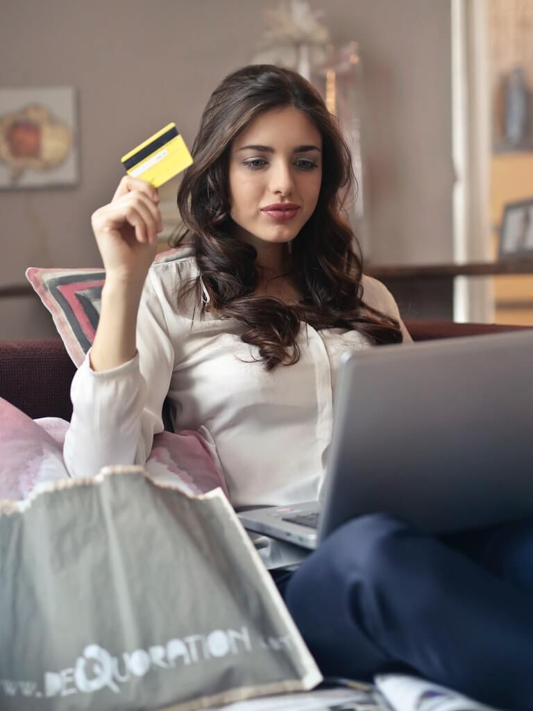Woman holding her credit card while using her laptop